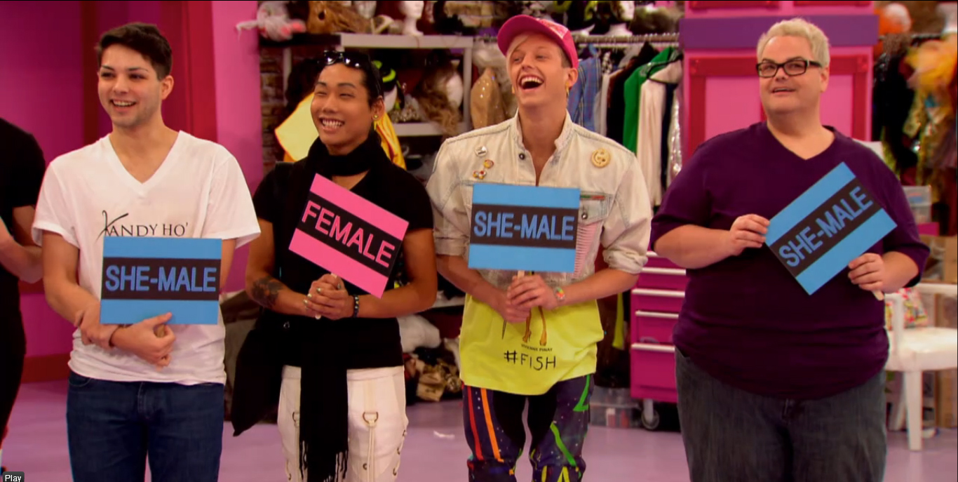 Image: RuPaul's Drag Race, Season 6 Episode 4 screenshot of four of the reality show's contestants holding up signs saying 'She-Male' and 'He-Male' for a show segment RuPaul introduced